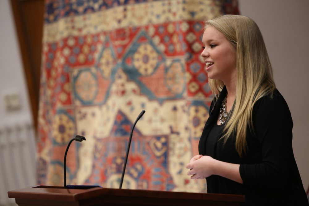 Student speaking publicly at an event to help Afghan women